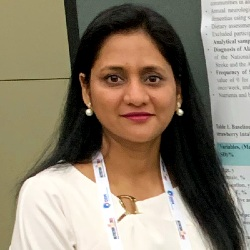 Dr. Puja Agarwal standing in front of an academic poster