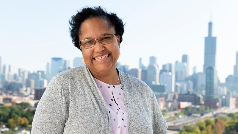 Kellye Walters-Warren standing on rooftop with Chicago skyline in background