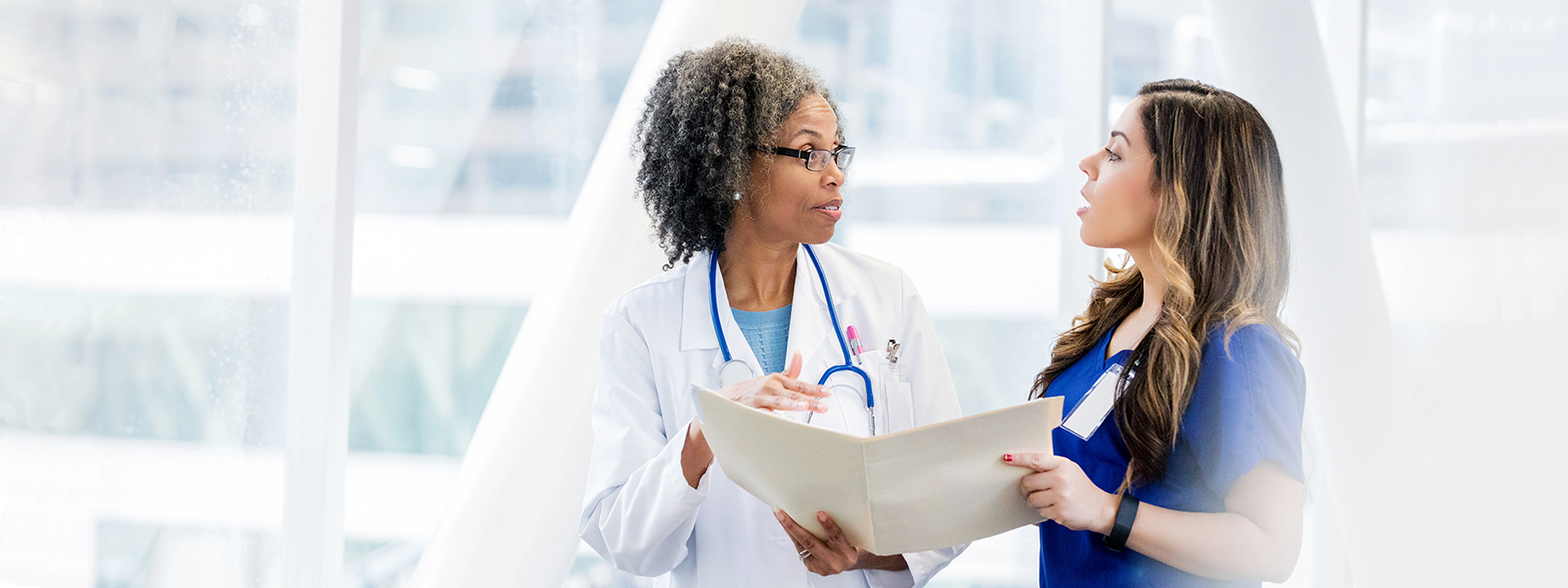 A doctor and nurse stand in a hallway discussing information in a folder