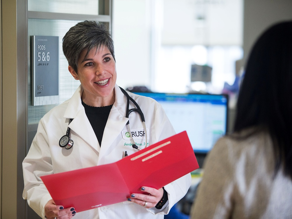 A smiling medical professional, wearing a white coat and holding a folder