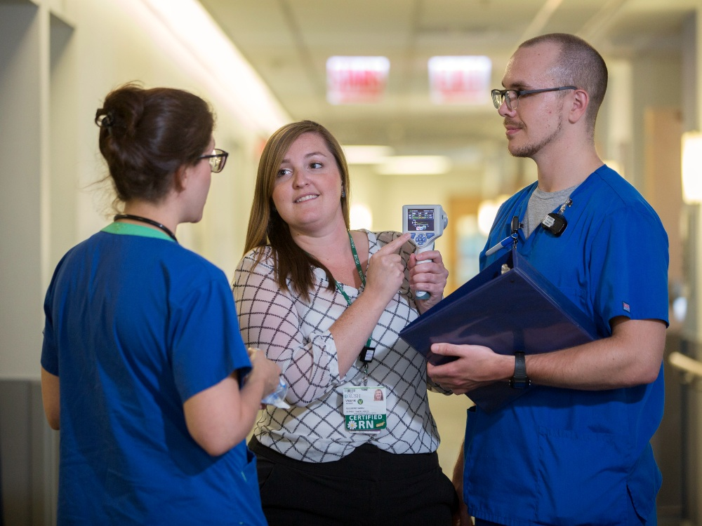 A nurse shows two colleagues a reading on a diagnostic device