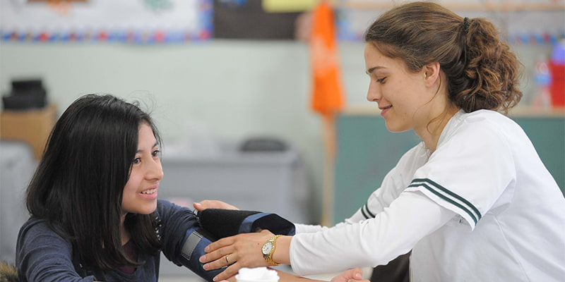 College of Nursing student takes a young girl's blood pressure