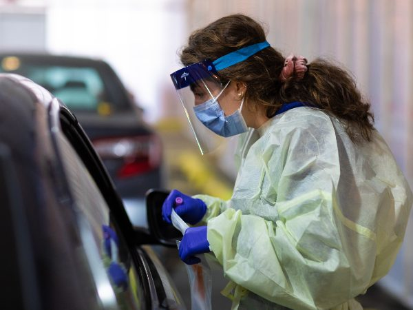 A nurse wearing protective equipment stands beside a car in a parking garage preparing a COVID test swab