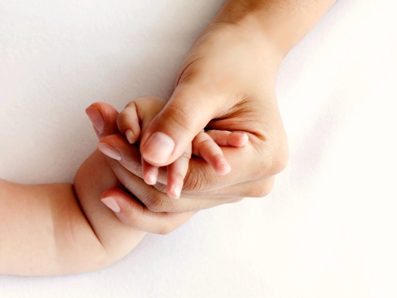 Close-up of a mother's hand holding her baby's hand