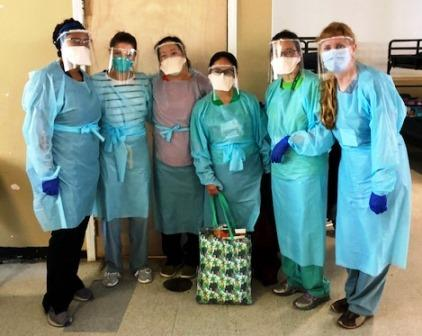People stand in PPE looking at the camera