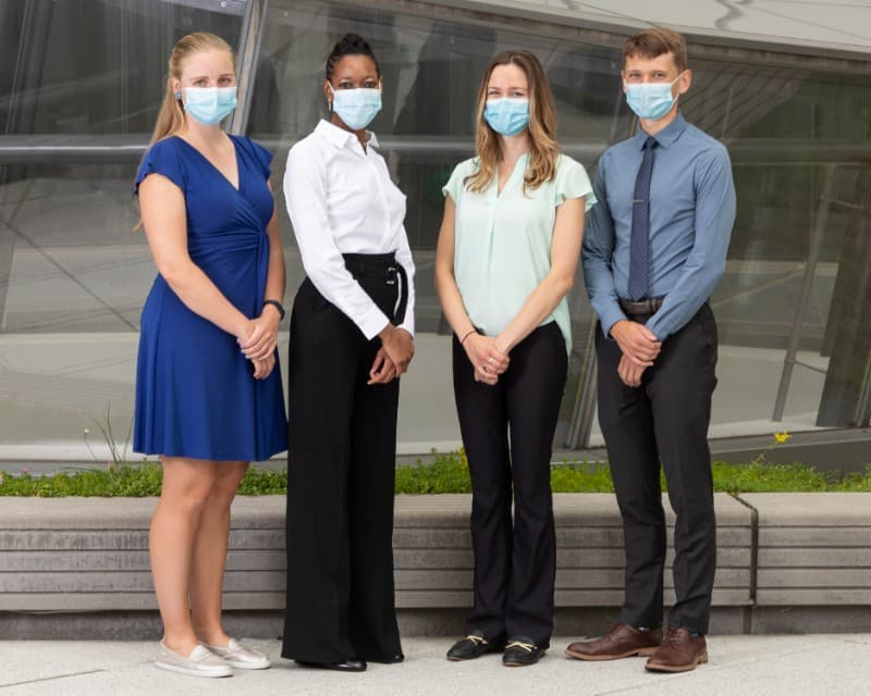 Four people wearing masks stand looking at the camera