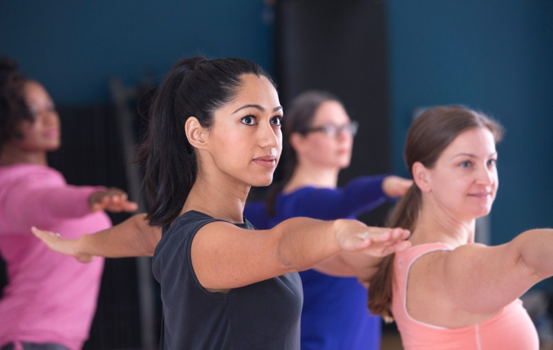 Students extending their arms in a yoga class