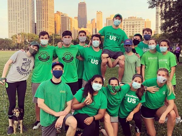 A softball team wearing Rush shirts and face masks pose together in a park