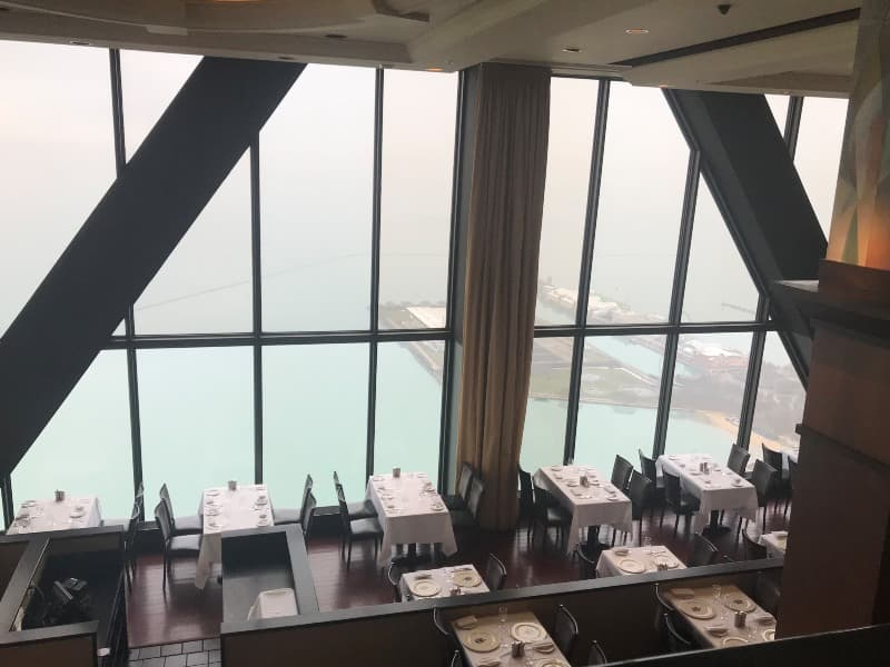 A restaurant dining room with a beautiful aerial view of Chicago through the windows
