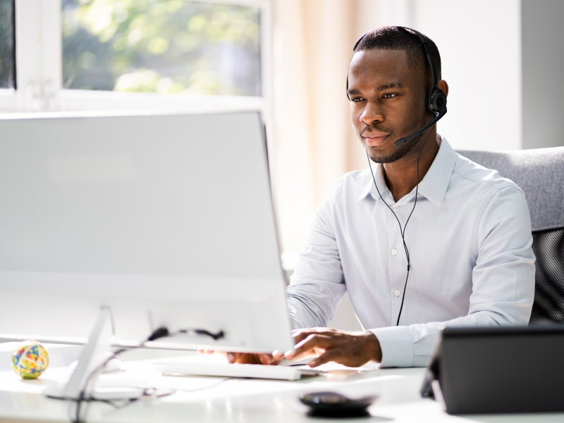 Man seated at an office desk using a computer and headset