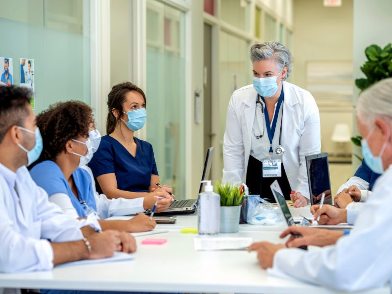 Medical professionals wearing masks seated around a table