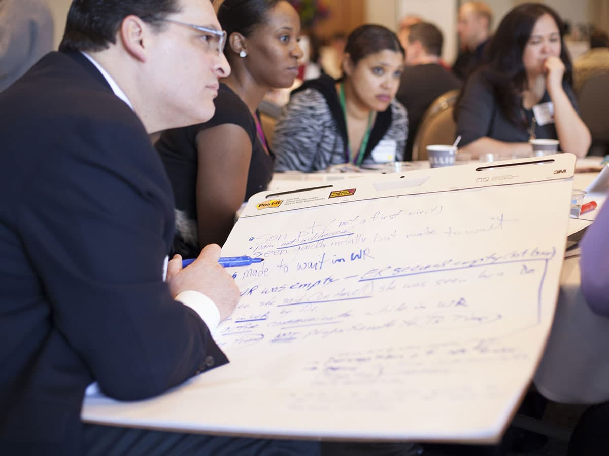 Employees participating in meeting while man writes on poster