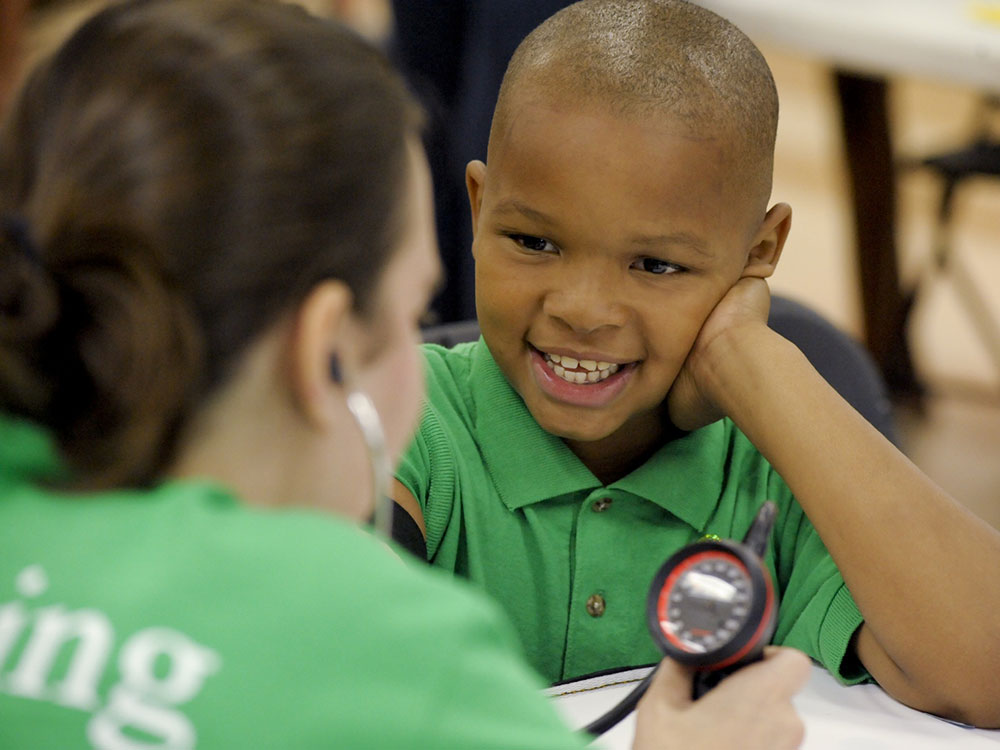 Student interacts with a young boy at the Health Fair