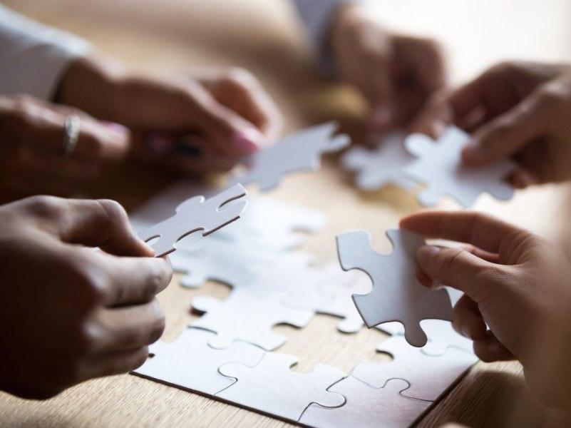 Hands assembling a jigsaw puzzle