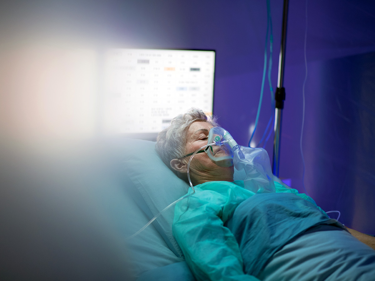 A patient lying in a hospital bed receiving supplemental oxygen