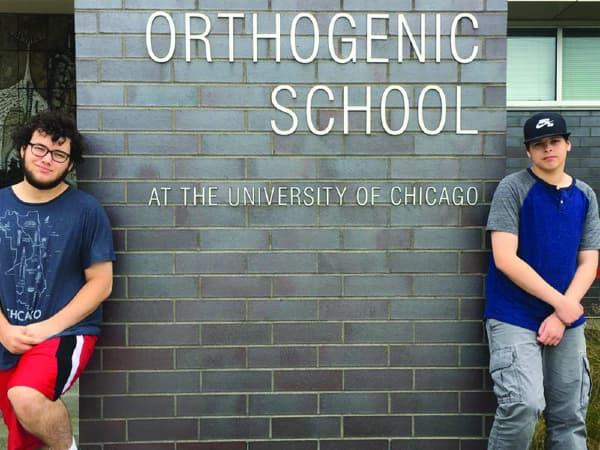 Two young men in front of the Orthogenic School