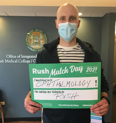 Student holding up sign with text: Rush Match Day 2021 - I matched into Ophthalmology - I'm taking my talents to Rush