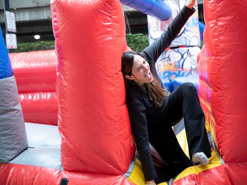 A student laughs while crawling through an inflatable maze