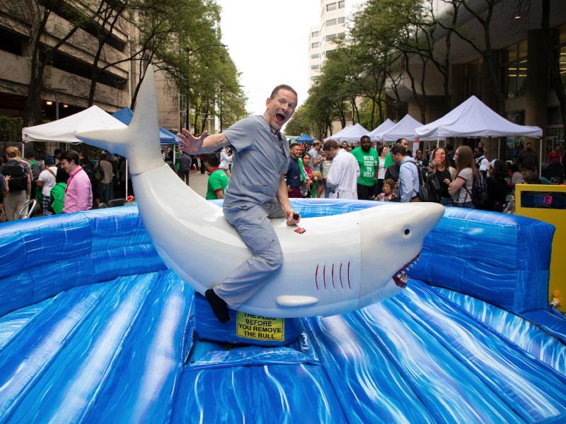 A man in scrubs rides a mechanical shark