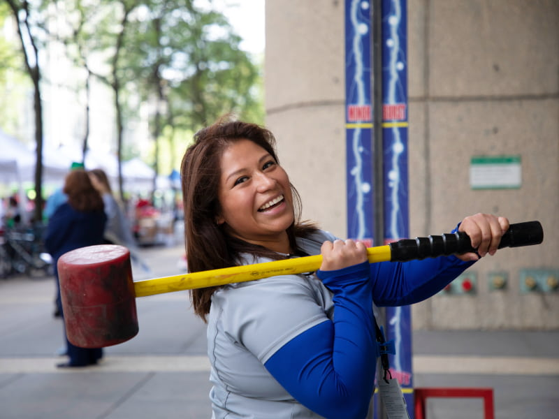 A smiling woman holds an oversized mallet over her shoulder