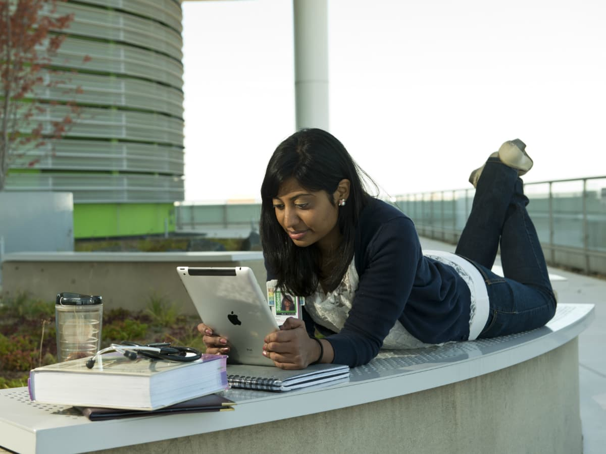 A Rush student studies outside
