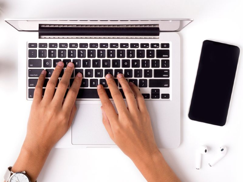Hands typing on a laptop keyboard, with a phone and wireless earbuds lying nearby