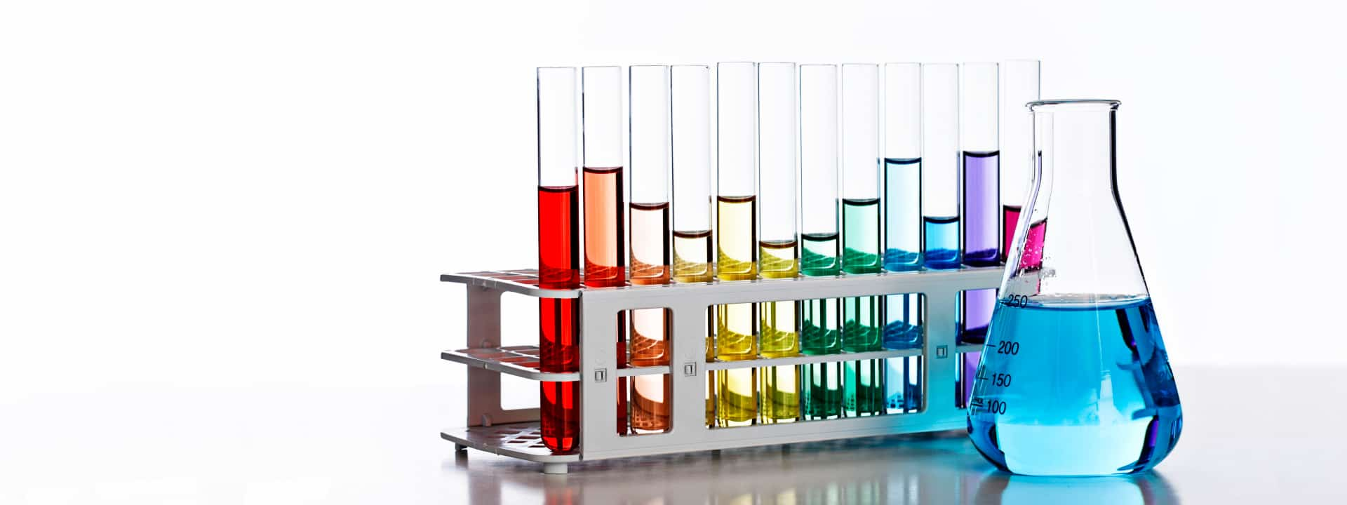 Flask and test tubes filled with liquids in rainbow colors
