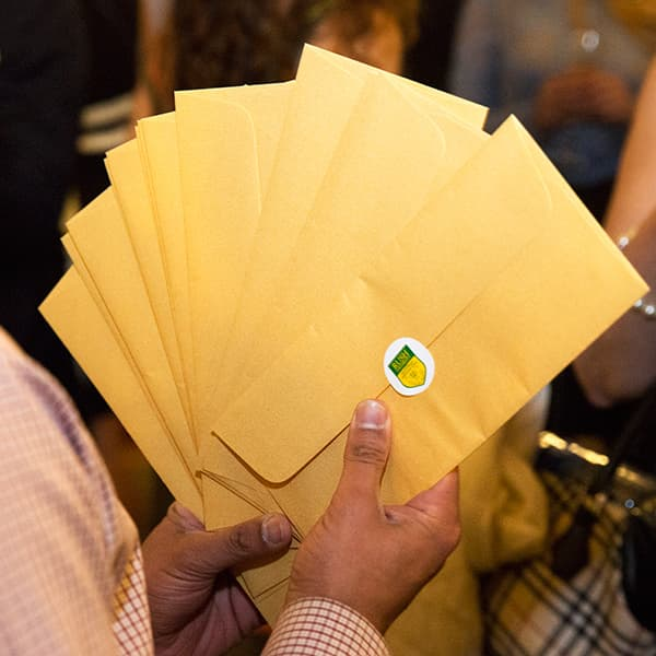 A stack of identical manila envelopes sealed wit the Rush University insignia