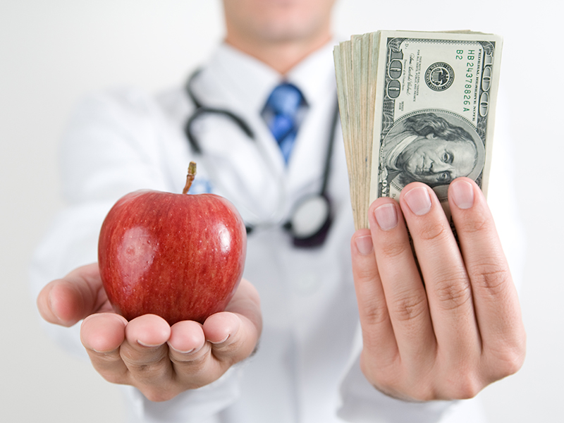 Doctor holding an apple and money