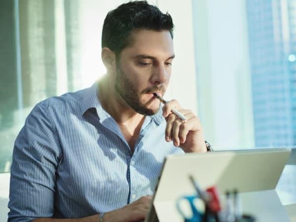 A man vaping while at his computer