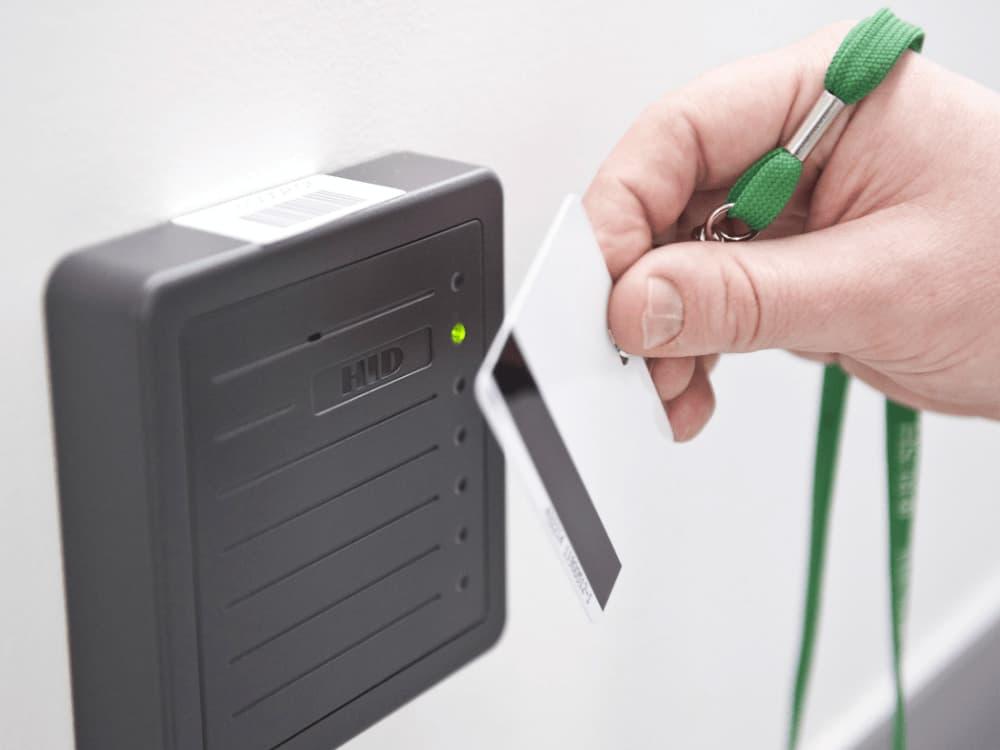 A hand swiping a key card.