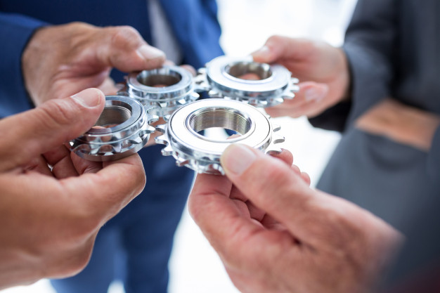 Four people holding a cog