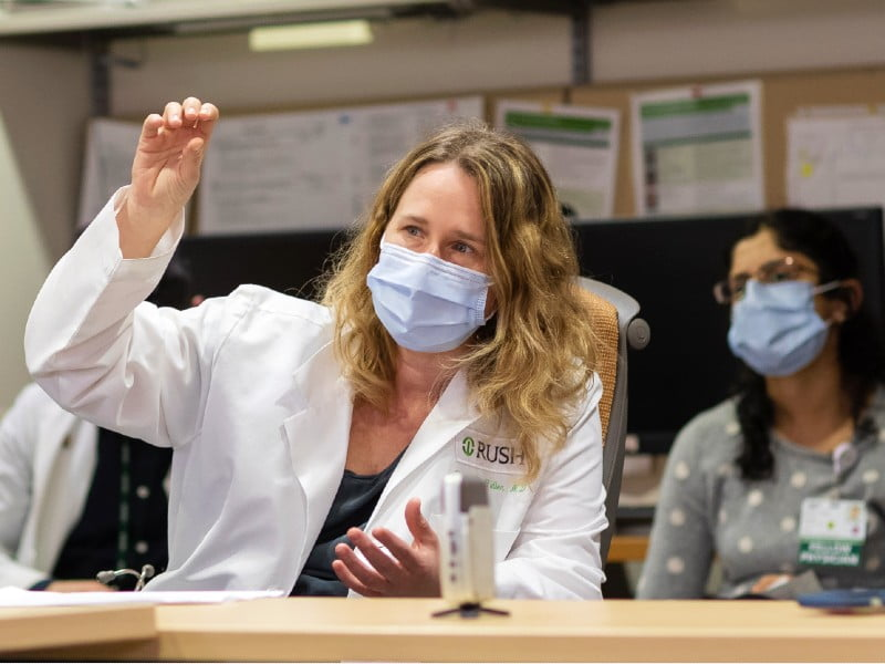Physician raising hand in a conference room