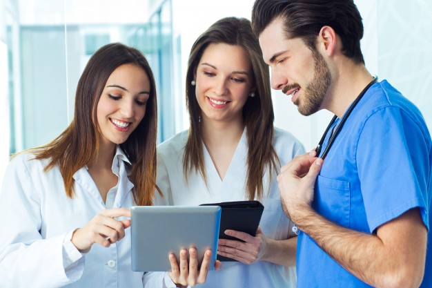 three healthcare workers or students collaborating on a tablet device