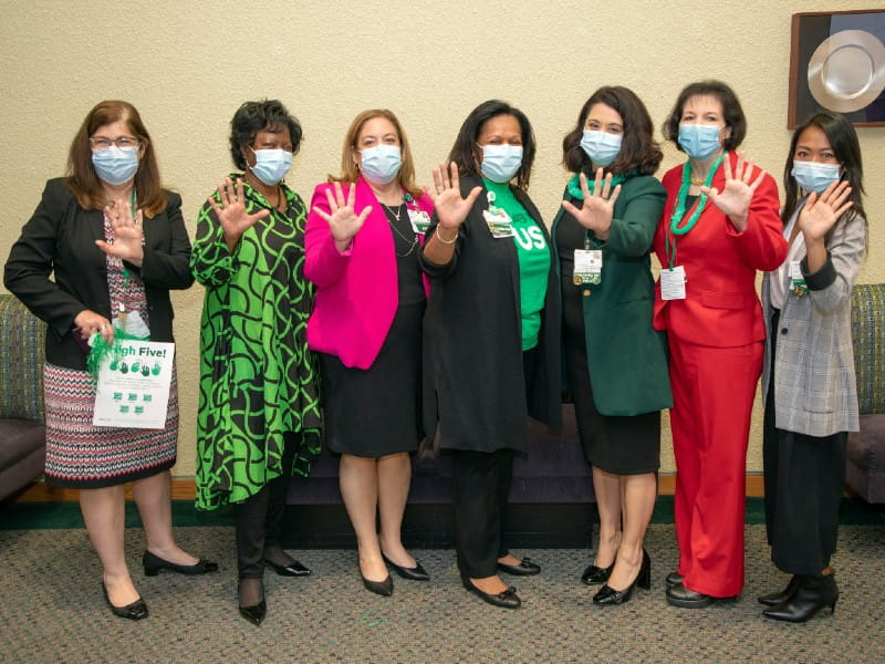 A group of faculty members wearing masks and waving to the camera