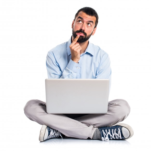 Man thinking sitting cross legged with a laptop on his lap