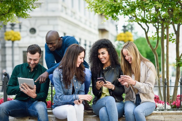 Multi ethnic group of students using a smartphone and tablet
