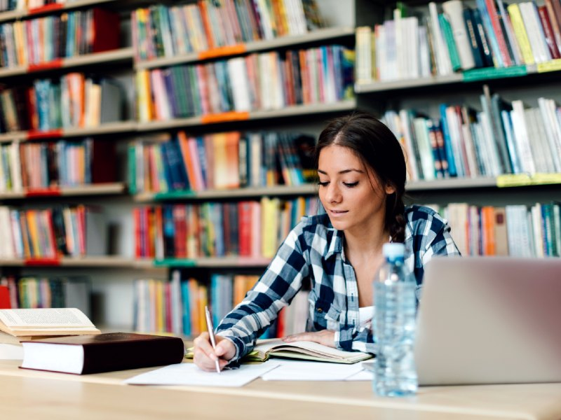 A student taking notes at a library table surrounded by bokshelves