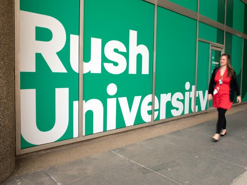 A woman walks outside past a window sign reading Rush University
